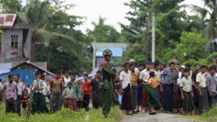 A soldier stands guard in front of Rohingya Muslims during UN envoy Tomas Ojea Quintana's visit to Aung Mingalar quarter in Sittwe on 13 August 2013.