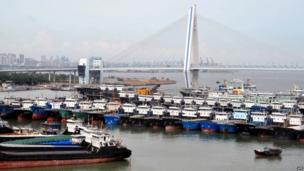 Fishing boats return from the sea and berth in a port in Haikou, south China's Hainan province, as powerful Typhoon Utor approaches the area on 13 August 2013