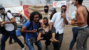People carry an injured protester at Nahda Square in Cairo during clashes between supporters of Egypt's ousted president Mohammed Morsi and riot police on 14 August 2013