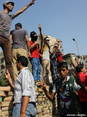 Protesters standing on a wall wave their arms in defiance