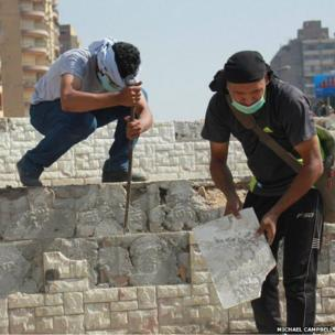 Protesters break up a concrete wall to access the material to throw as missiles at security forces