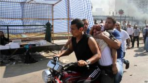 Egyptian Muslim Brotherhood supporters drive a wounded comrade on a motorbike near Ramses square in Cairo on August 16, 2013.