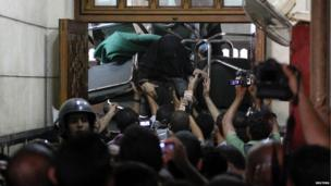 A woman climbs from behind a barricade set up by supporters of deposed Egyptian President Mohamed Morsi inside the al-Fath mosque in Cairo (17 August 2013)