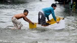 Children riding a makeshift furniture boat across floodwater.