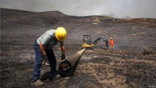 Idaho Power workers replace burned power poles at the Beaver Creek wildfire outside Hailey, Idaho 17 August 2013