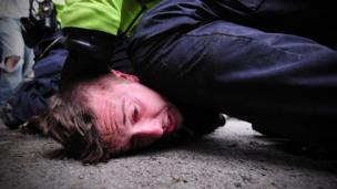 Police officer kneeling on man's head