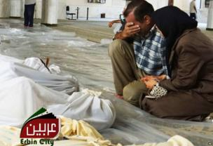Image provided by Syrian opposition activists purportedly showing man and woman mourning next to bodies wrapped in shrouds in Irbin, Damascus (21 August 2013)