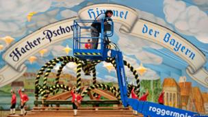 A worker stands on a lifting ramp in the Hacker-Pschorr beer tent during the preparation for the 2013 Oktoberfest beer festival on 22 August, 2013 in Munich, Germany. Munich Oktoberfest, which opens to the public on 21 September, draws millions of visitors and is the biggest beer festival in the world
