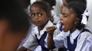 An Indian schoolgirl eats a free midday meal at school on the outskirts of the city of Jammu.