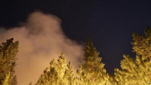 Trees lit up at night under a starry sky as Rim Fire burns in California on 25 August 2013