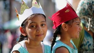 Two young girls watch on at the festival, they are wearing paper crowns