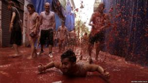 Group of people covered in tomato juice