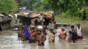 Flood-affected villagers carry their belongings in the Indian state of Bihar