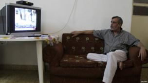 A Syrian refugee, who fled the violence in Syria, watches a news broadcast on the Syria crisis at the Al Hussein Palestinian refugees camp in Amman, Jordan, on 29 August, 2013
