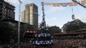 A large crowd with a human pyramid in the middle
