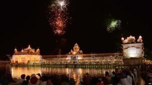 Indian Sikh devotees watch a fireworks display above the illuminated Sikh shrine The Golden Temple in Amritsar on September 1, 2013. on the occasion of 409th anniversary of the Guru Granth Sahib, the holy book of the Sikh religion.