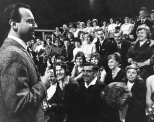 Compere David Jacobs talking to the audience in Studio 2, Television Centre, during the warm up before the live showing of Juke Box Jury. 01/01/1964