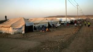 Picture taken on 27 August shows Kurd refugees from Syria sitting outside tents provided by the UNHCR at the Quru Gusik refugee camp, east of Arbil