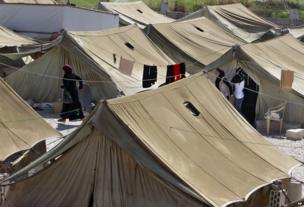 Syrian refugees women stand outside their tents, at a temporary refugee camp in the eastern Lebanese town of Marj near the border with Syria, Lebanon