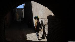 An Afghan boy carries brooms on his shoulder for sale in the old part of Herat