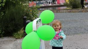 Isla standing by balloons