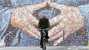 A cyclist rides past a giant election billboard