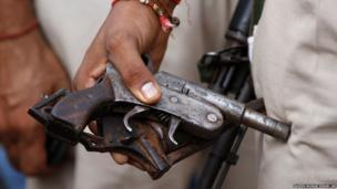 An Indian policeman holds recovered arms during a door-to-door search operation in Muzaffarnagar