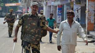 Indian soldiers detain two individuals following communal riots between Muslims and Hindus in Muzaffarnagar, India's Uttar Pradesh state, on September 9, 2013.