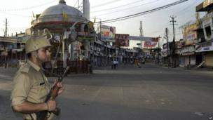 In this Saturday, Sept. 9, 2013 photo, an Indian policeman stands guard during a curfew hours following riots and clashes between two communities in Muzaffarnagar