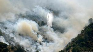 A helicopter drops water on the Morgan fire as it advances down a hillside at Mount Diablo State Park near Clayton, California