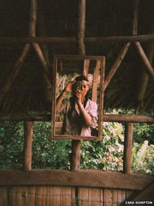 Woman takes a self portrait in a mirror