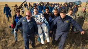 Expedition 36 Flight Engineer Alexander Misurkin is carried to a medical tent