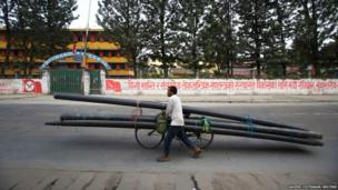 A man transports pipes on his bicycle during a general strike in Kathmandu