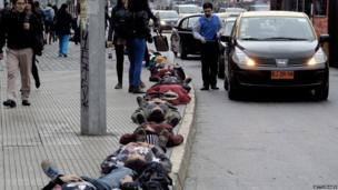 Part of a group of 1210 people can be seen laying down on the sidewalk along Alameda street during a commemorative action in Santiago, on 10 September 2013
