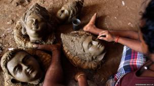 An artisan works on clay idols of the Hindu god Vishwakarma