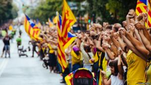 Thousands of people form a human chain, many waving flags. Photo: Richard Hadley