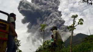 Indonesian farmers rush to harvest crops in the district of Karo as an ash cloud rises during a fresh eruption of the Mount Sinabung volcano on 17 September, 2013.