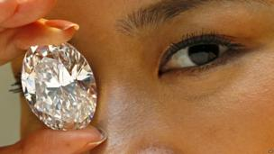 A model holds up a white diamond larger than her eye.