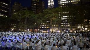 A park full of people dressed in white.