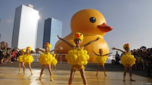 Girls dress as ducks as people gather to see a giant Rubber Duck by Dutch conceptual artist Florentijin Hofman at Glory Pier on September 19, 2013 in Kaohsiung, Taiwan.