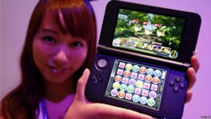 A girl holds a Nintendo 3DS displaying Puzzle and Dragons Z