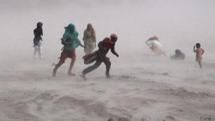 People walk through a storm near the Ravi River in Lahore