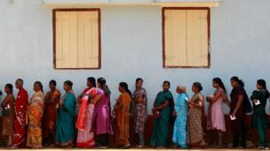 Sri Lankan ethnic Tamil women wait to cast their votes at a polling station