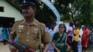 A police officer stands guard as Sri Lankan ethnic Tamils wait in line to cast their votes
