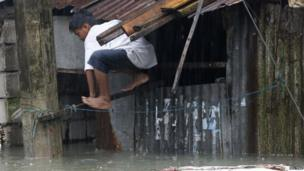 Boy climbs out of the window as flood water rises.