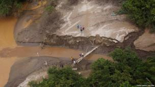 Residents cross a makeshift bridge in the village of Omitlan, in the Mexican state of Guerrero