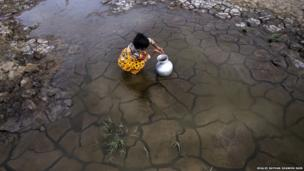 Girl collects water from a puddle