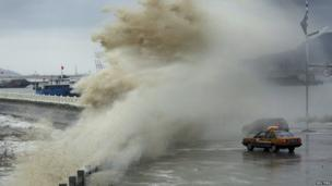A typhoon sprays waters over cars.