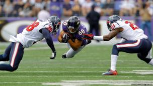 Brandon Stokley (centre) of the Baltimore Ravens dives for a first down