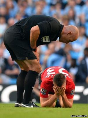 Referee Howard Webb speaks to Manchester United's English midfielder Tom Cleverley